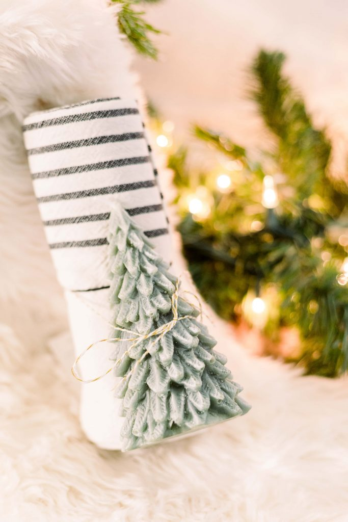 Christmas Tree Candle tied to rolled black and white striped tea towel on a white fur stocking