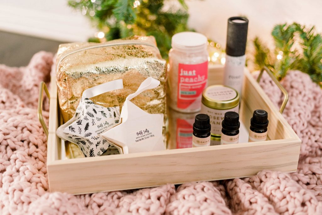 gold cosmetic bag bath salts incense candle and essentials oils arranged on a light wood tray laying on a blush blanket as a holiday gift