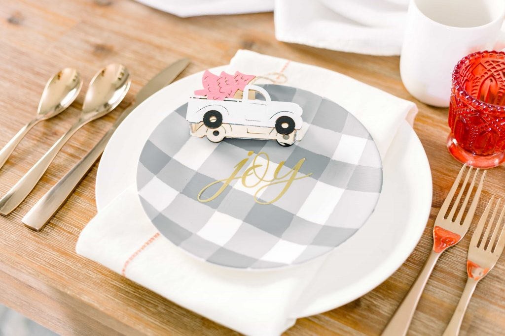 white dinner plate with white napkin and grey buffalo check accent plate and wood truck ornament painted white with a pink christmas tree in the back
