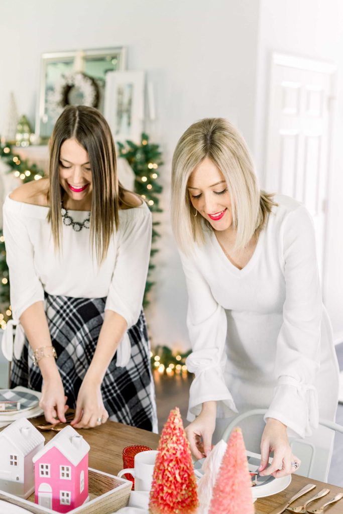 brunette and blonde females setting a table for christmas