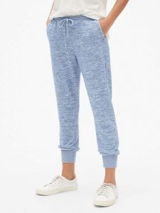 close up of womans lower body wearing light blue jogger sweatpants and white shoes