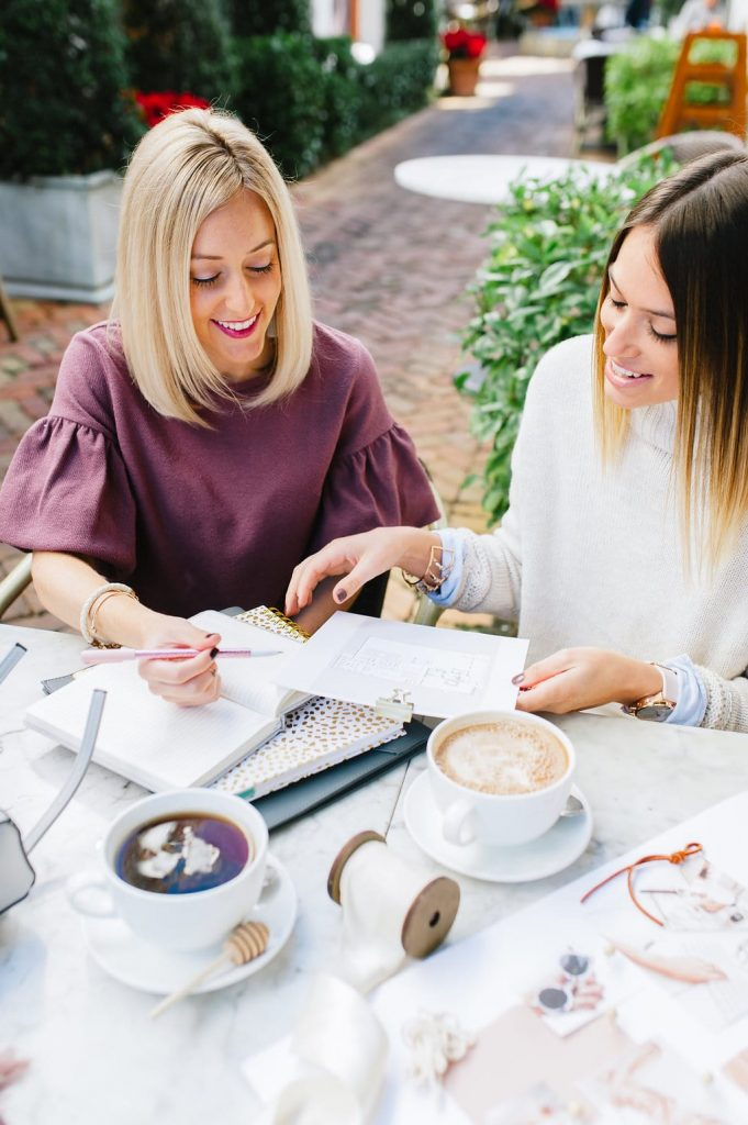 blonde female in maroon blouse with brunette female in ivory sweater sitting at a coffee shop having a business meeting