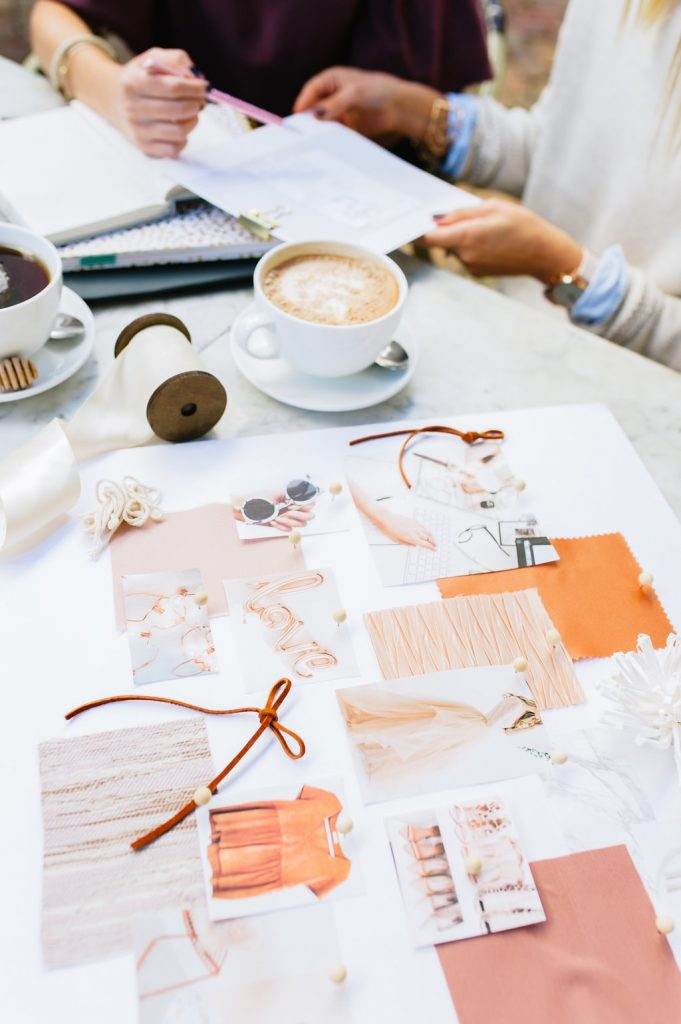 pink and orange mood board set on white marble table at coffee shop with two females having a business meeting and enjoying a cup of coffee and tea