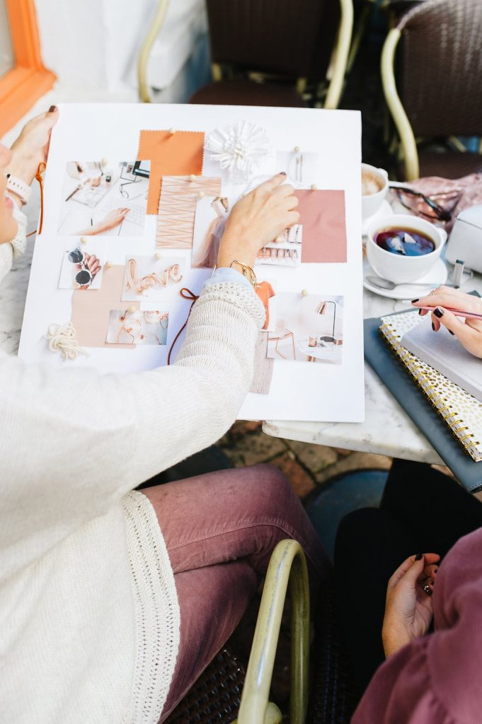 female in ivory sweater at a coffee shop holding a large pink and orange mood board pointing to one of the images