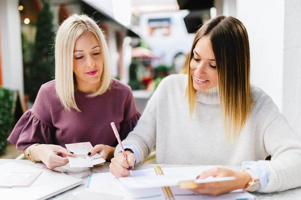 blonde female in maroon blouse holding two pieces of paper next to brunette female in ivory sweater writing in spiral planner with pink pen in a coffee shop courtyard