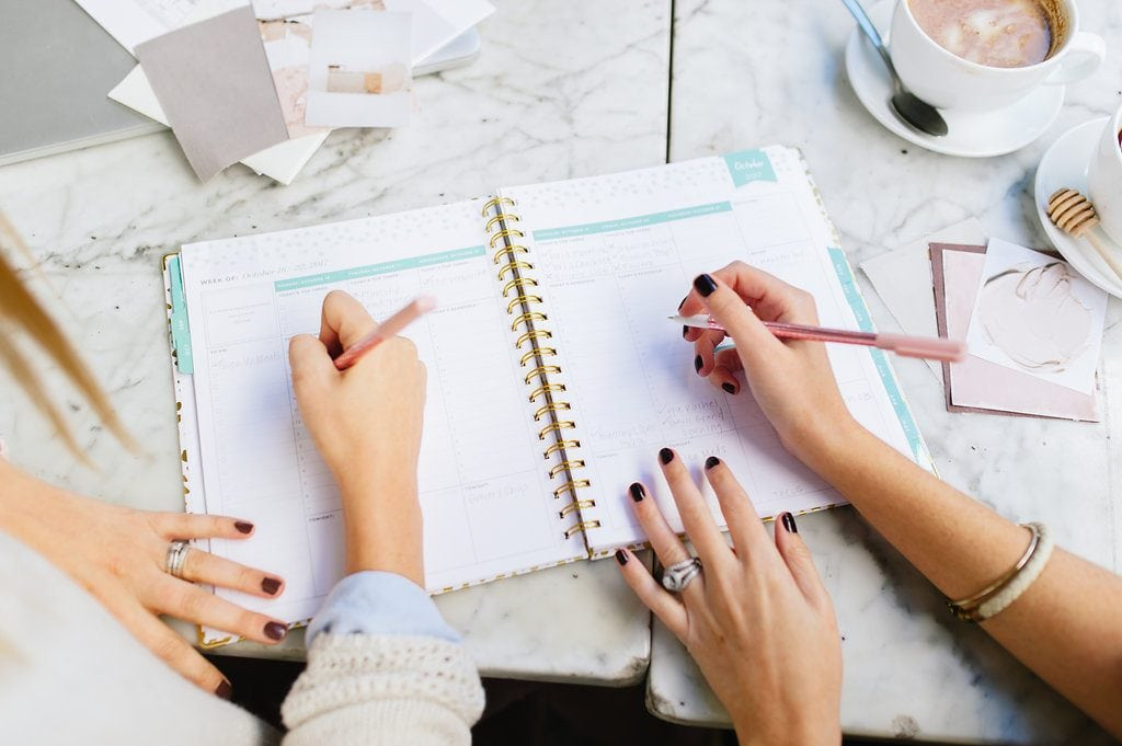 close up of two females marking a spiral planner on a white marble table at a coffee shop