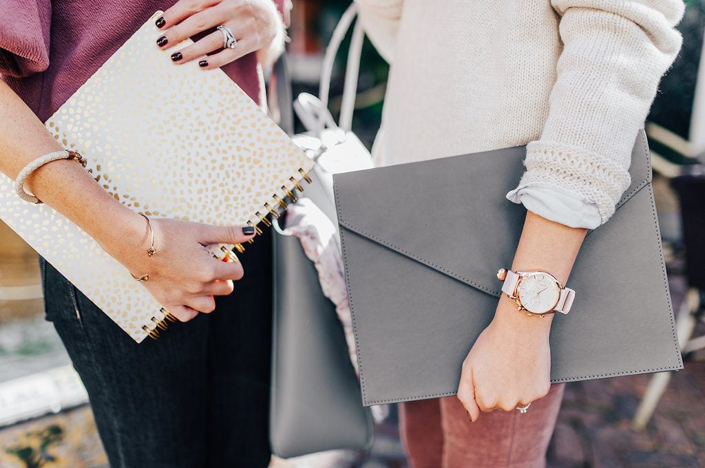 close up of female in maroon top holding a day designer planner and female in ivory sweater with oversized pink and gold watch holding a grey envelop portfolio