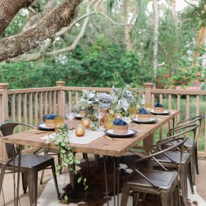 wood table with hairpin legs on outdoor deck with industrial metal chairs and cowhide rug set with dishes from bloomingdales the registry