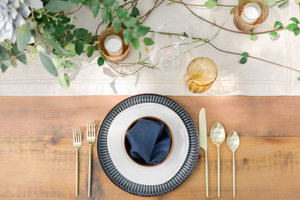overhead shot of blue and white place setting on rustic wood table with modern gold flatware