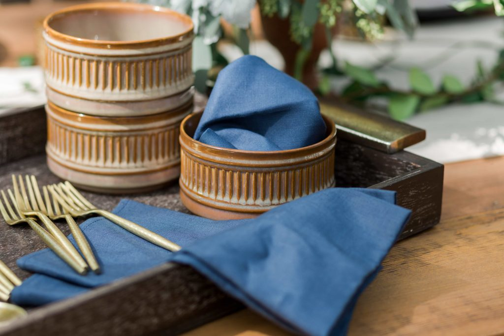 set of terra cotta bowls blue linen napkins and gold flatware in wood serving tray