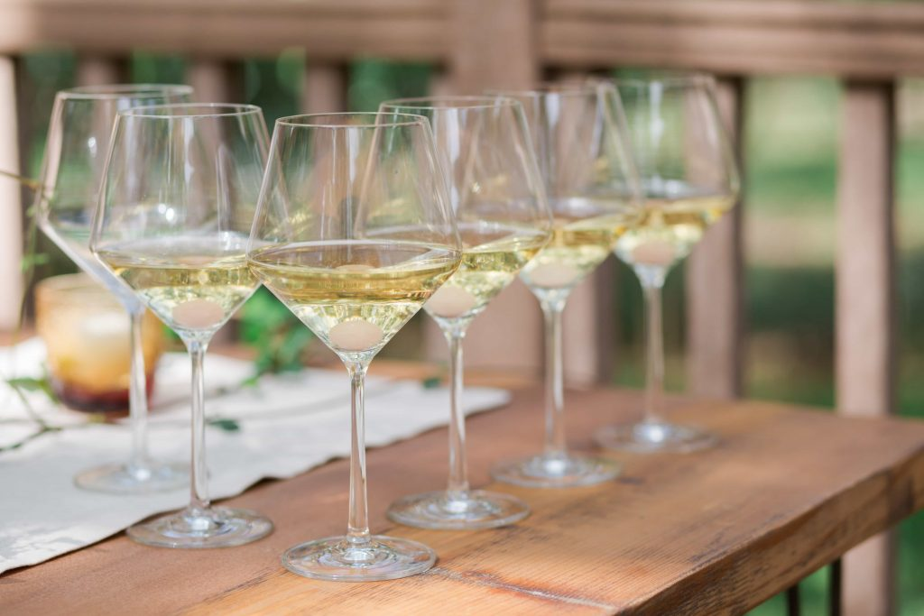 six wine glasses full of white wine lined on rustic wood table