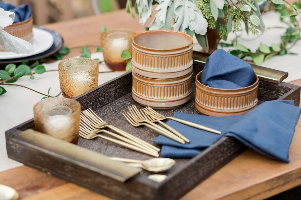 dark wood tray with gold handles full of terra cotta bowls blue linen napkins and gold flatware on wood table from bloomingdales the registry