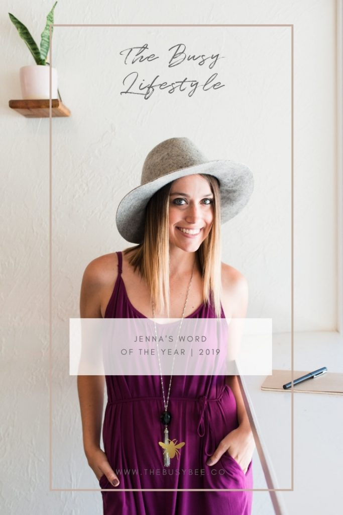 blogger wearing purple romper from target and gray hat with notebook on desk