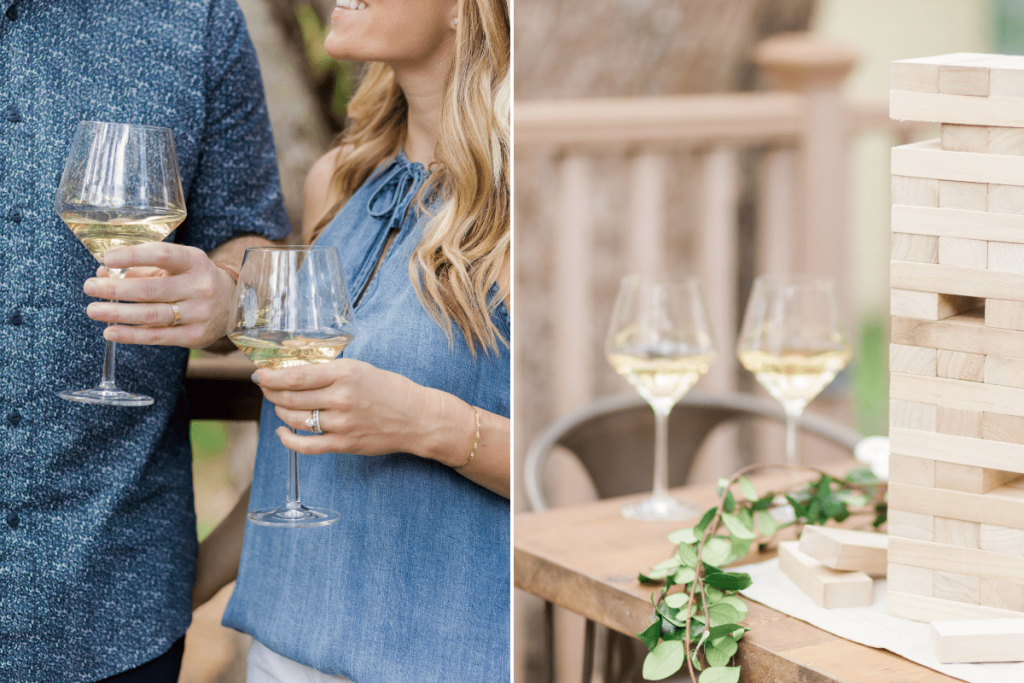 close up of male and female holding glasses of white wine wearing blue tones and two white wine glasses next to set of jenga on rustic wood table