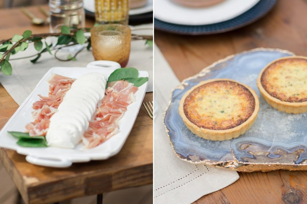 white platter with mozzarella and prosciutto and blue and gold geode slab with quiche on rustic wood table