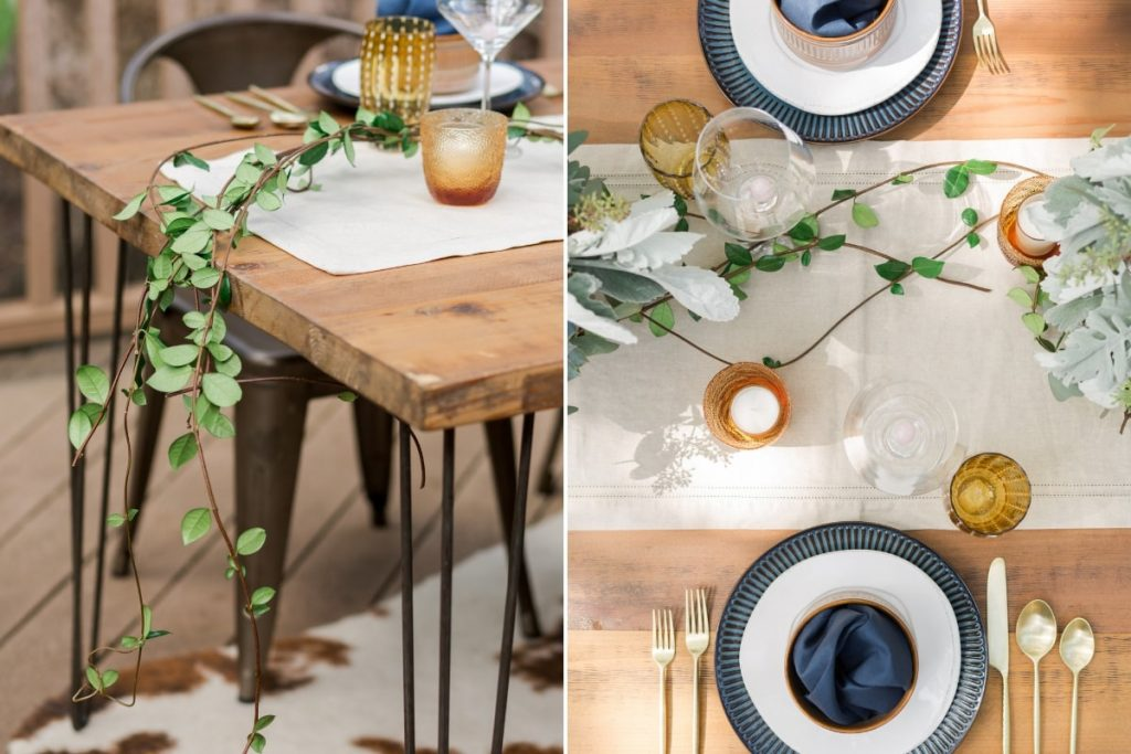 rustic wood table set with green vine neutral linen table runner and blue and white place setting with modern gold flatware