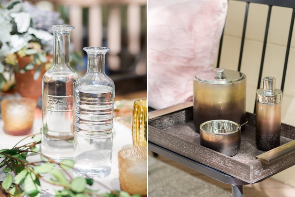 two water decanters on rustic wood table next to broze gold and silver ombre ice bucket and cocktail shakeer in wood serving tray