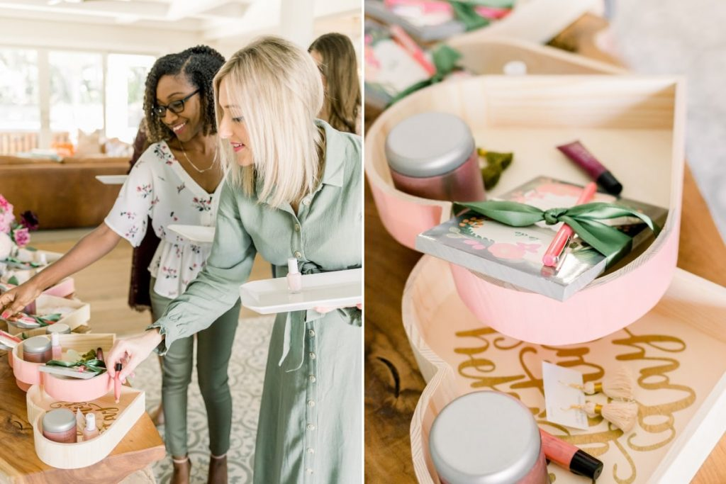 two young women wearing olive green placing beauty products and accessories in wooden heart boxes for a favorite things party
