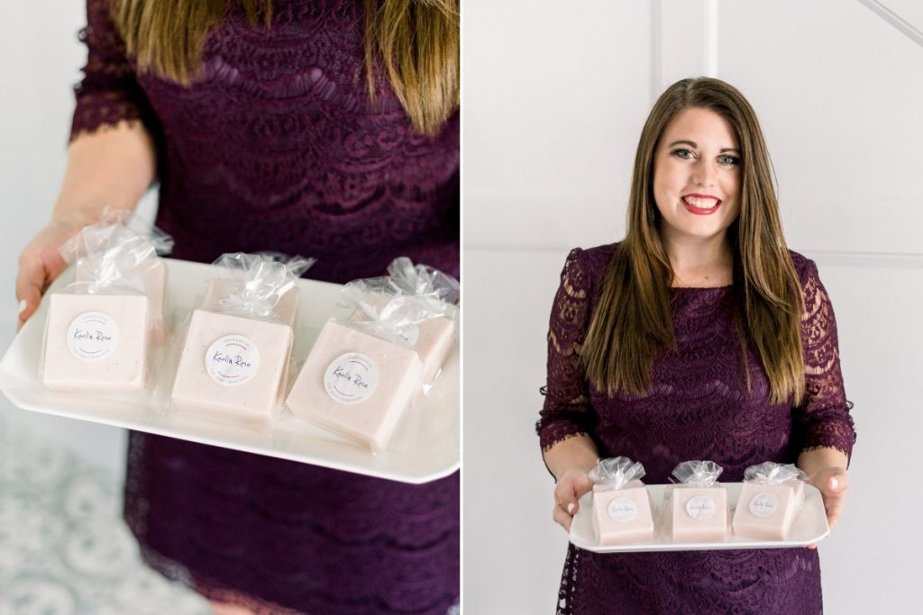 brunette female in dark maroon dress holding white tray of blush ariem body co soap