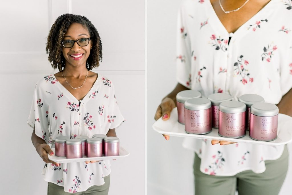 young female in glasses and white pink and green floral top holding white tray of sparkling rose tea from par avion tea