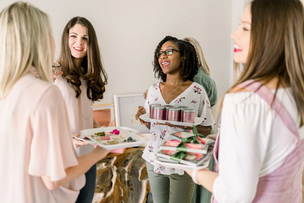 a group of young women standing in a circle laughing and having a fun conversation while holding white trays of their favorite products