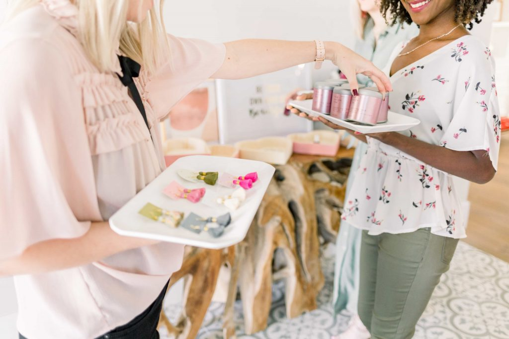 two young females in blush and olive green holding white trays full of tassel earrings and par avion tea exchanging gifts