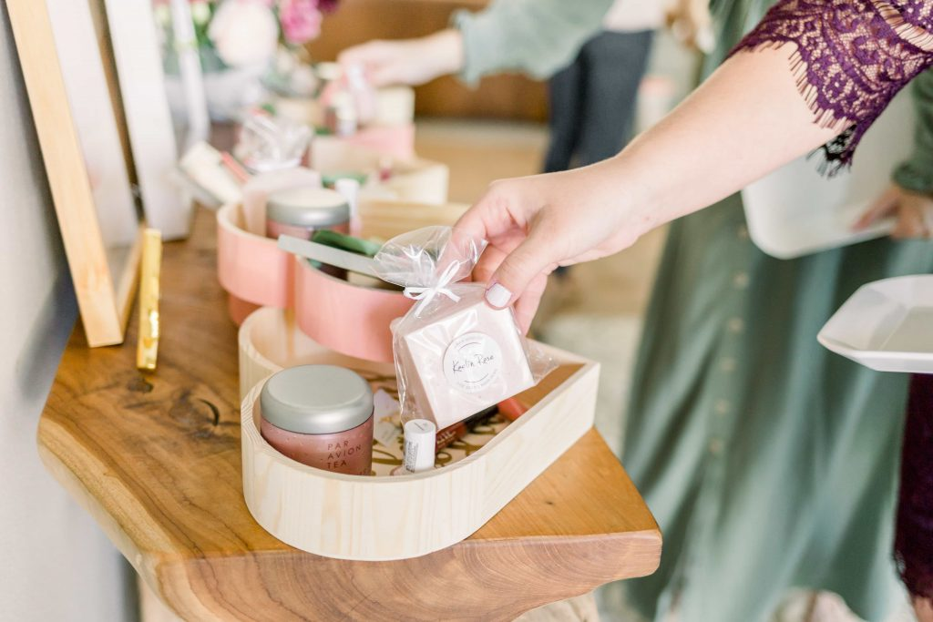 close up of womans hand placing bar of ariem body co soap in a wooden tray full of beauty products and accessories