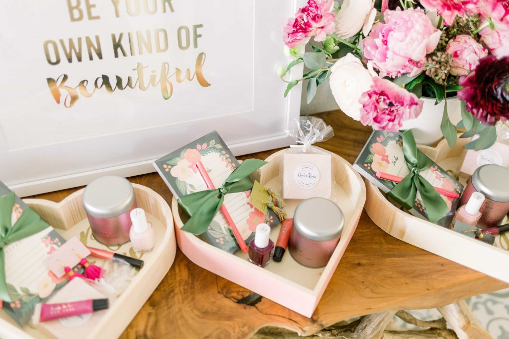 close up of three wooden heart boxes full of various accessories and beauty products set in front of a be your own kind of beautiful print and floral arrangement for a favorite things party