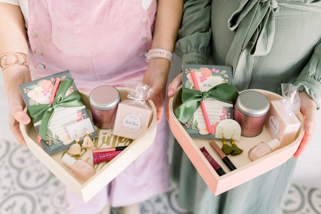 close up of two women wearing blush corduroy overalls and an olive green dress holding wooden heart boxes full of products for a galentine's day favorite things party