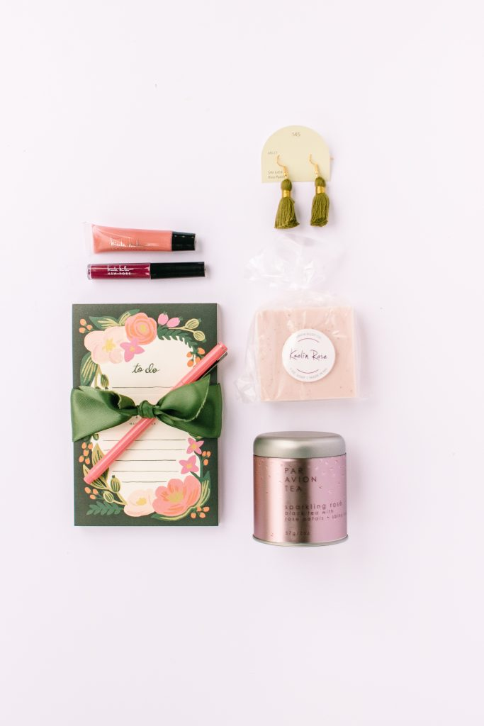 flat lay photo of rifle paper co to do notepad sparkling rose par avion tea kaolin rose ariem body co soap olive green pecox tassel earrings and nicole miller lip gloss
