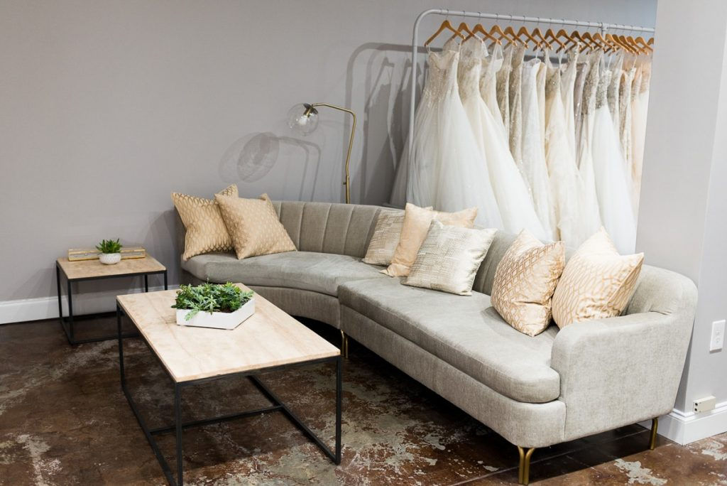modern grey velvet couch and wood and black iron coffee table and end table set in front of a rack of wedding dresses
