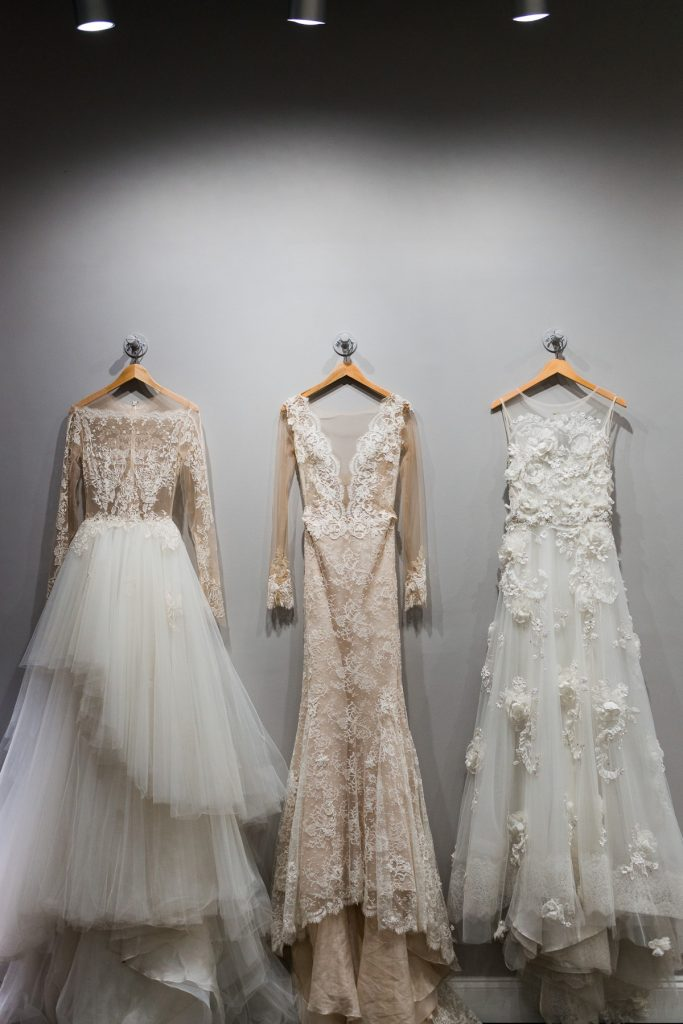 three designer wedding dresses hanging on a wall hooks side by side