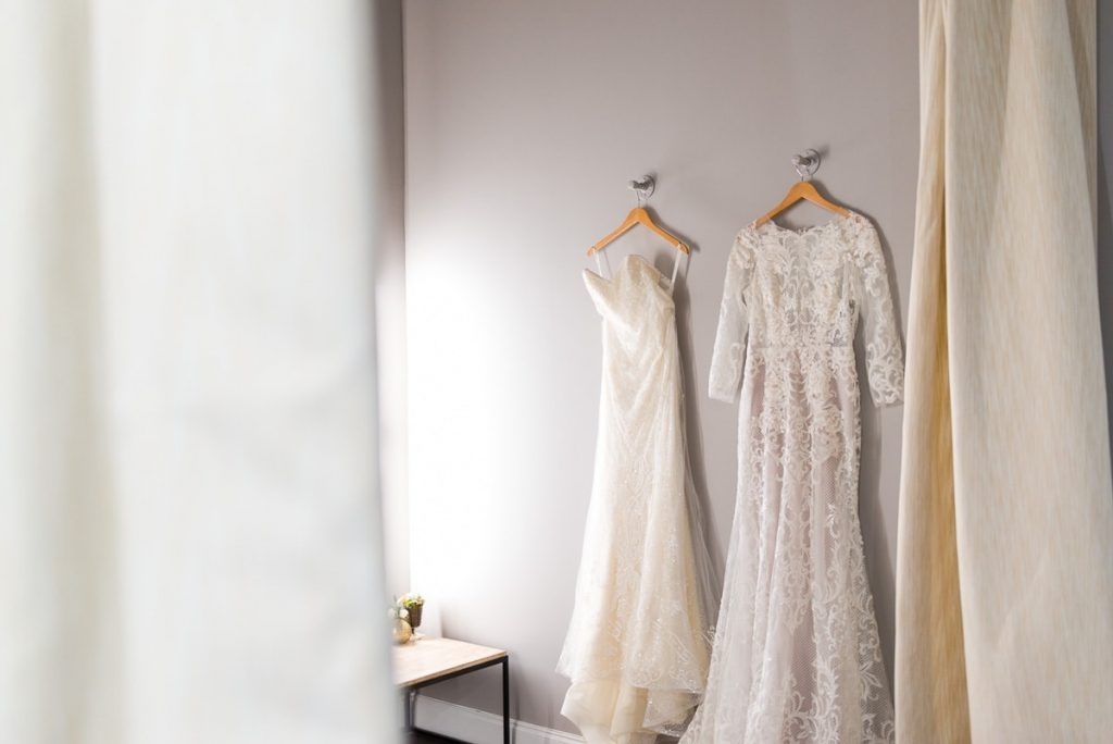 two designer wedding dresses hanging on wall hooks in the bridal finery winter park bridal boutique fitting room