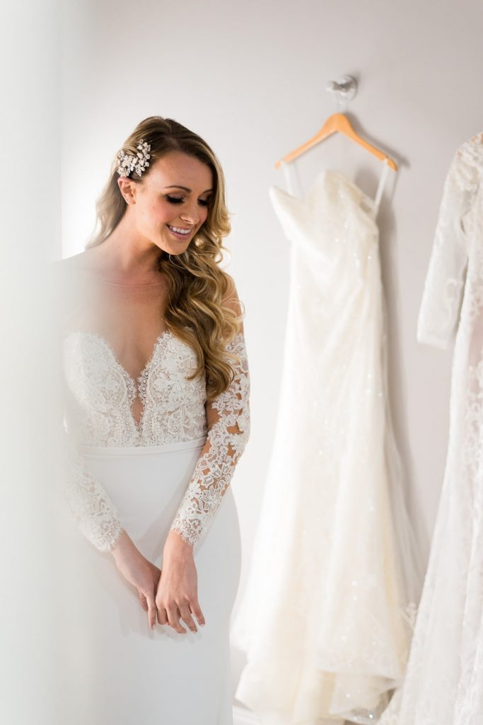 woman with long blonde curly hair in white lace wedding dress looking down and smiling from winter park bridal boutique fitting room