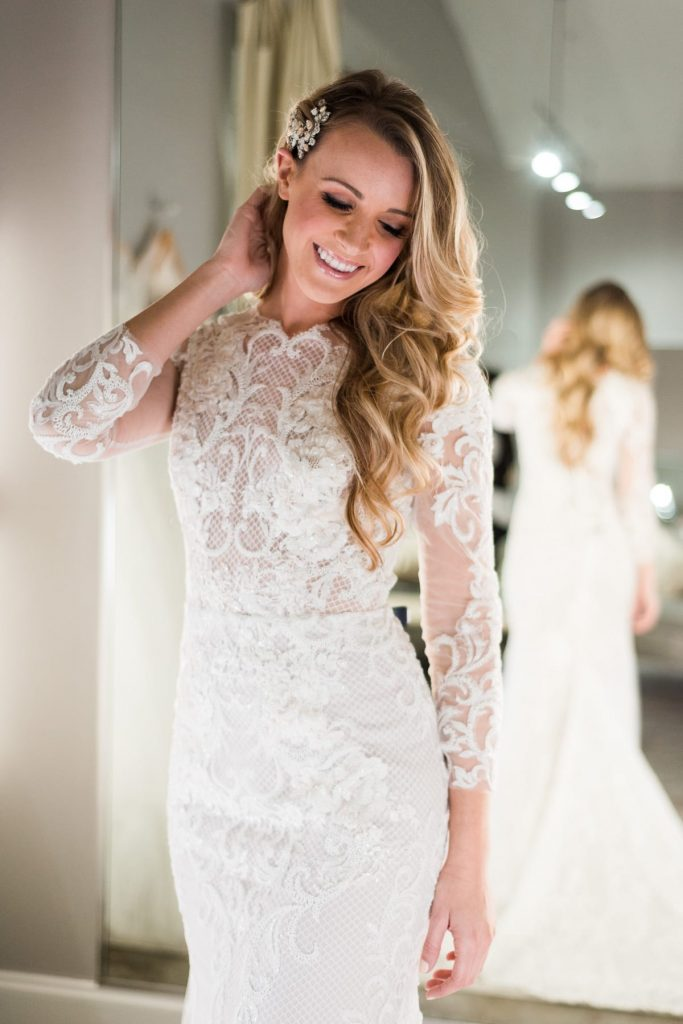 woman with long blonde curly hair trying on white lace wedding dress in the bridal finery winter park bridal boutique fitting room