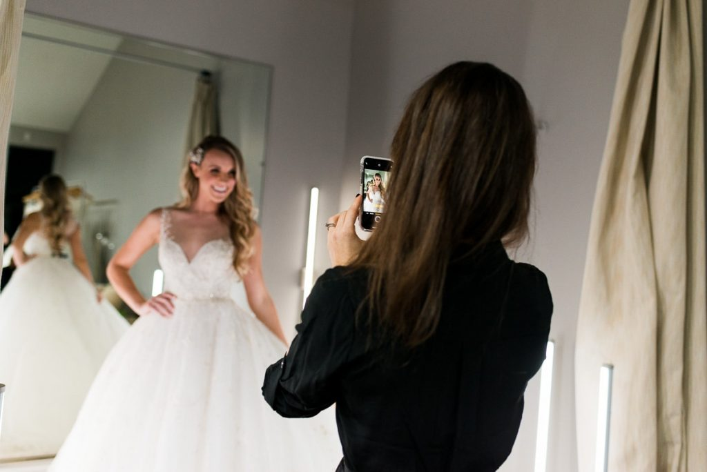brunette woman taking a cellphone photo of woman with long blonde hair trying on white wedding dress at the bridal finery winter park bridal boutique fitting room