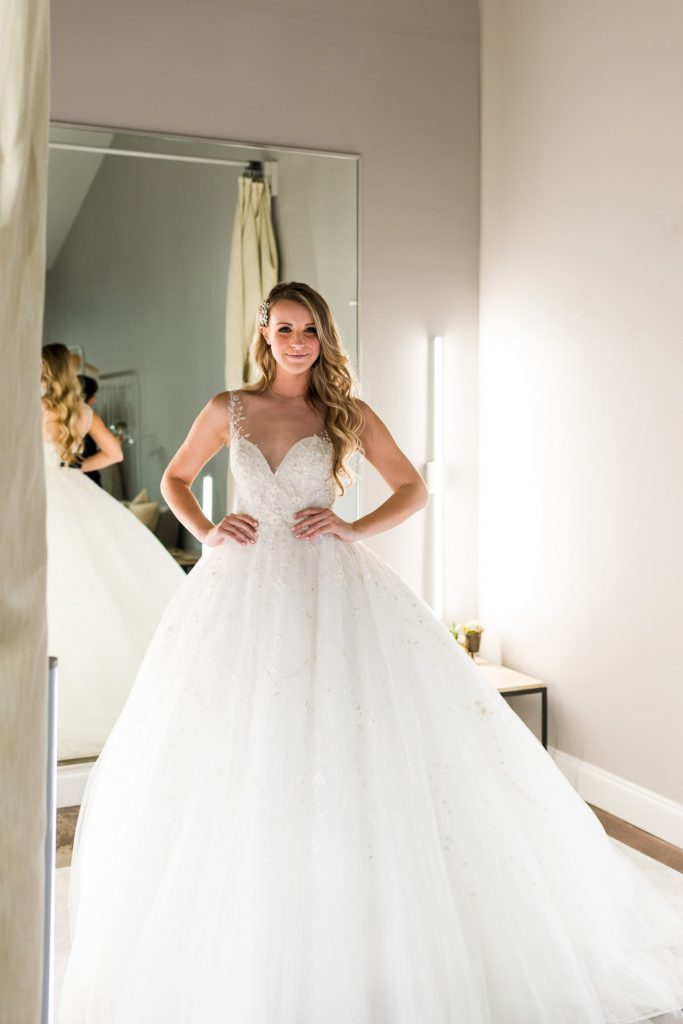 woman with long blonde curly hair trying on a white wedding dress ball gown with hands on hip in winter park bridal boutique fitting room