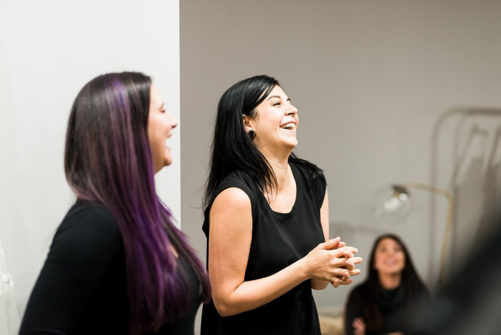 two brunette women dressed in black looking off to the right laughing