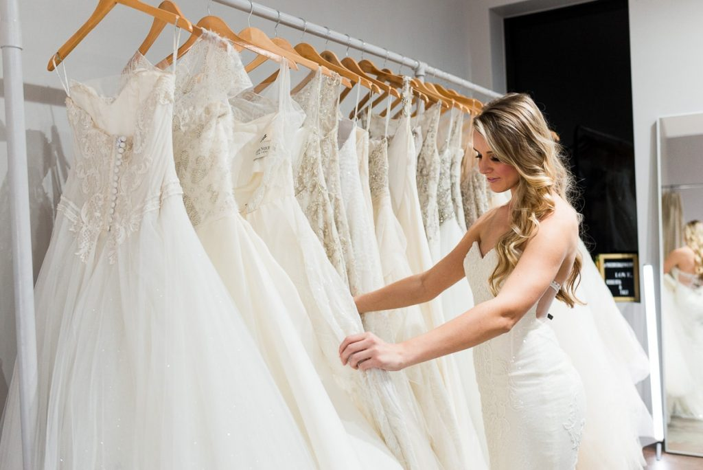 woman with long blonde curly hair wearing a wedding dress and looking through a rack of designer wedding dresses