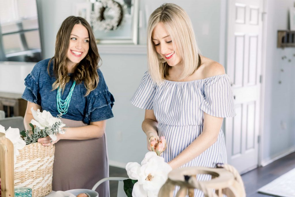 young brunette woman in denim top and tan skirt looking over shoulder and smiling at young blonde female in blue and white off the shoulder dress while putting together easter basket
