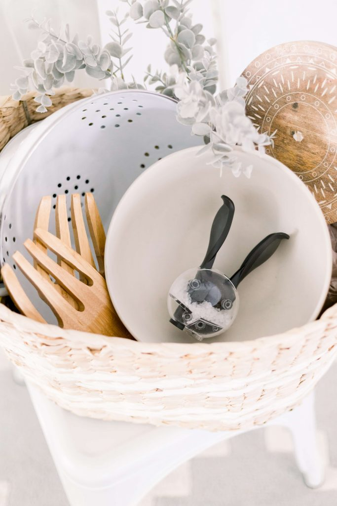 light tan and white woven basket filled with hostess essentials white colander stone bowl wood salad servers wood cutting board and bunny salt mill