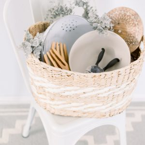light tan and white woven basket filled with hostess essentials white colander stone bowl wood salad servers wood cutting board and bunny salt mill set on top of white industrial chair
