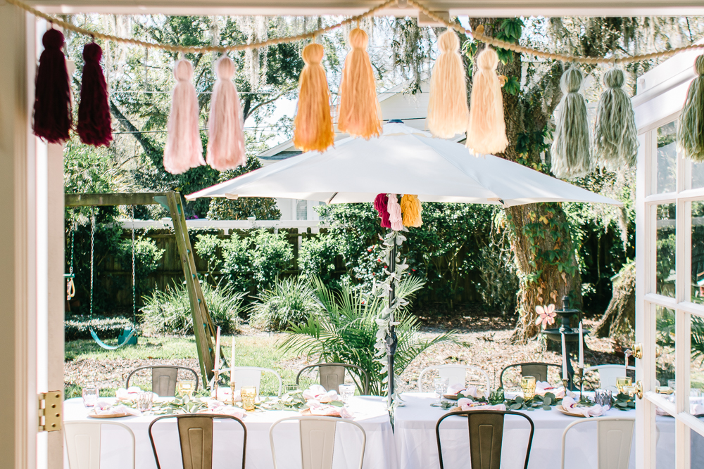 Earth Tone Baby Shower decorations with oversized yarn tassels and a simple tablescape using colored glassware and greenery.