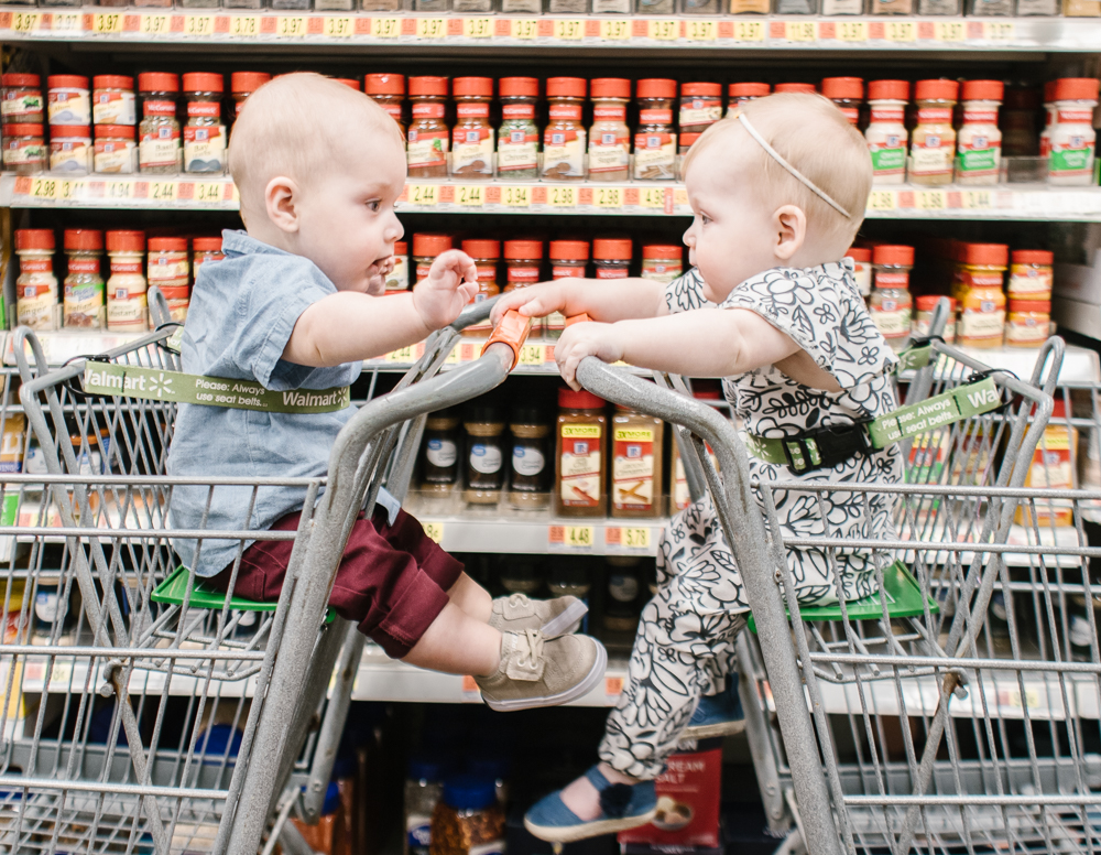 two babies sitting in walmart carts playing