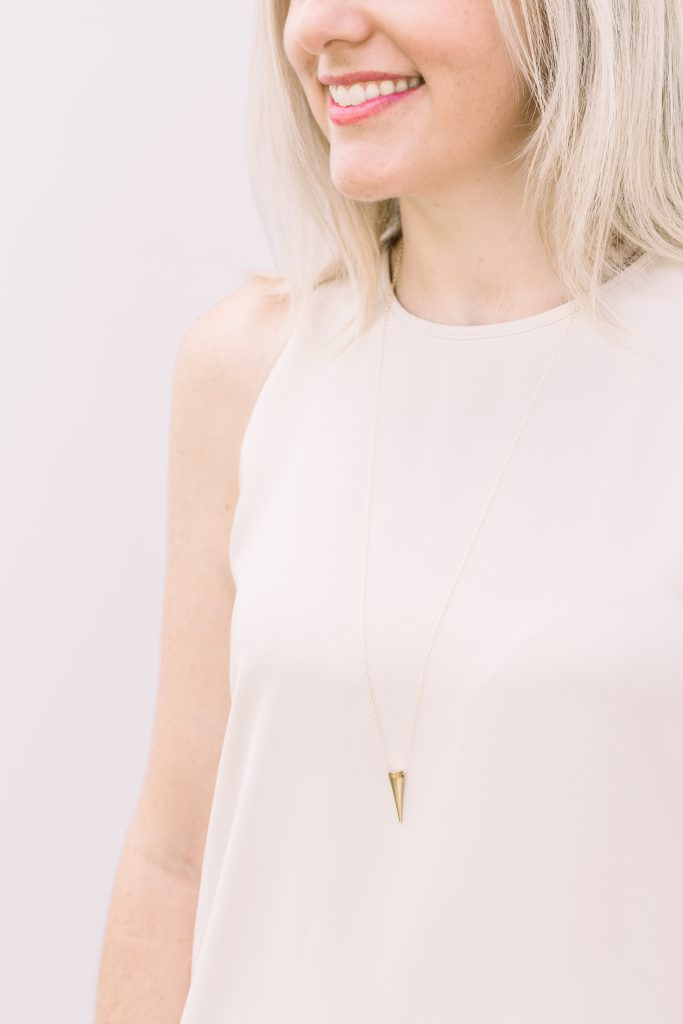 blonde woman wearing white shirt and infant loss necklace