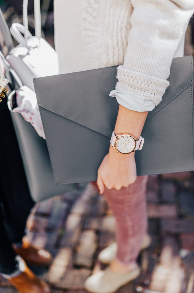 close up of woman holding grey leather portfolio with rolled up sweater and pink and gold watch
