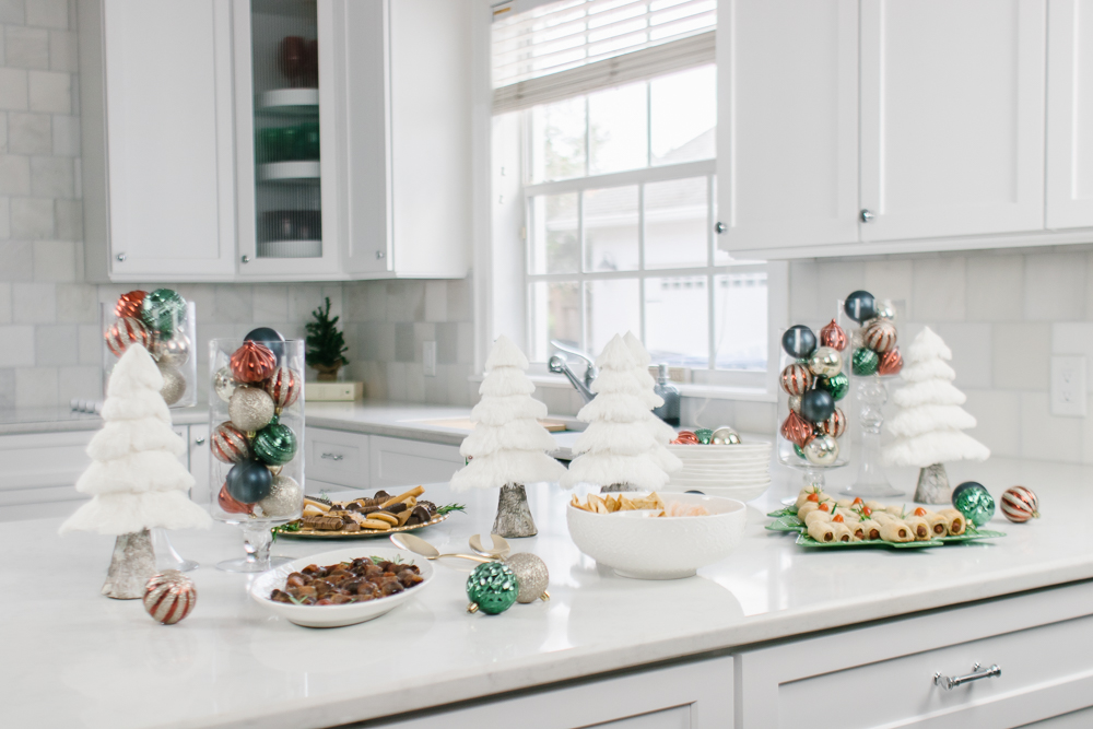christmas buffet set on white marble countertops in white kitchen