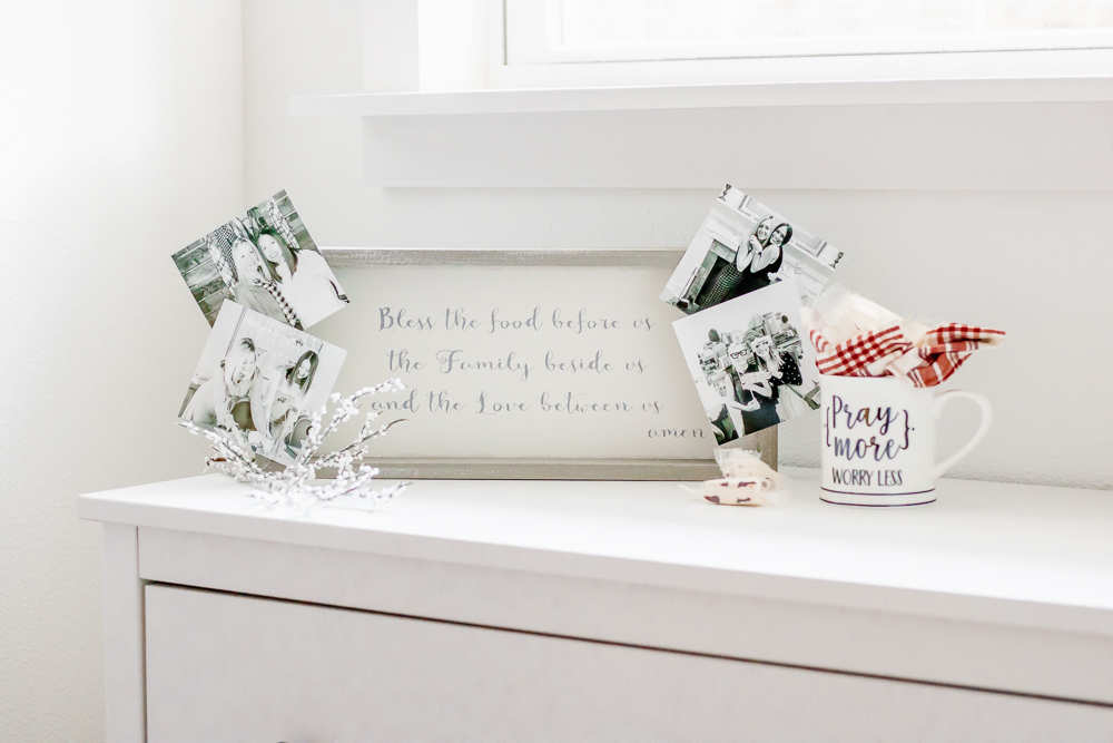 wood and white faith sign on white dresser with black and white photos attached and pray more mug full of candy