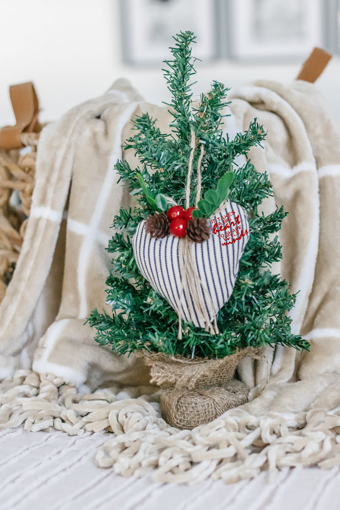 close up of wick basket filled with tan and white plaid blanket with a mini christmas tree and black and white heart ornament set in front