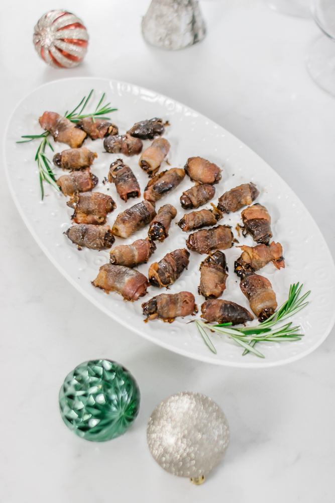 close up of bacon wrapped dates on white platter